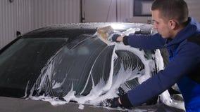 De wasauto van de mensenarbeider met spons op een autowasserettepost stock videobeelden