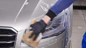 De wasauto van de mensenarbeider met spons op een autowasserettepost stock footage