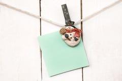 De wasknijpers die van de Kerstmissneeuwman leeg notadocument houden Royalty-vrije Stock Foto