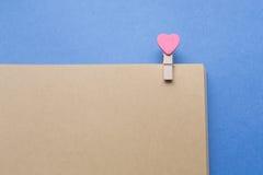 De wasknijpers met harten zijn Blocnote Blauw document als achtergrond Royalty-vrije Stock Foto