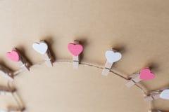 De wasknijpers met harten zijn Blocnote Blauw document als achtergrond Stock Afbeelding