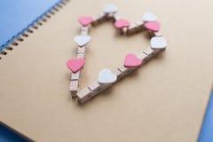 De wasknijpers met harten zijn Blocnote Blauw document als achtergrond Stock Fotografie