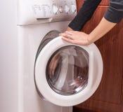 De wasmachine met vrouwenhanden, opent royalty-vrije stock foto