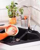 De wasschotel van vrouwenhanden met spons in moderne keuken royalty-vrije stock fotografie