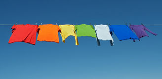 De wasserij van de regenboog, heldere overhemden op een drooglijn Stock Foto's