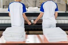 De wasserijarbeider zet gestreken textiel stock afbeeldingen