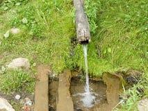 De waterbron die van een houten pijp stromen Stock Foto