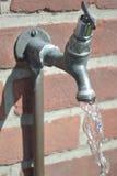 De waterkraan maakte aan een bakstenen muur met lopend water van uit de kraan vast Stock Foto