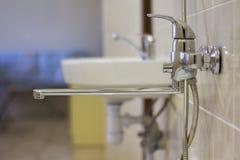 De waterkraan, verchroomt roestvrije die metaaltapkraan met douchebox betegelde muur wordt verbonden, mixer koud warm water op va stock fotografie