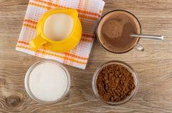 De waterkruik met melk op servet, kommen met cacao poedert zich en suiker, cacao met melk, lepel in kop op lijst Hoogste mening stock foto's
