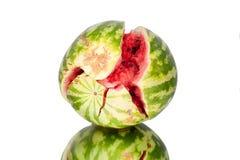 De watermeloen met barsten op witte spiegelachtergrond met bezinning isoleerde dicht omhoog royalty-vrije stock afbeelding