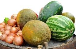 De watermeloenen, meloenen, uien, groene paprika liggen op bodem van omgedraaide houten vaten Stock Foto