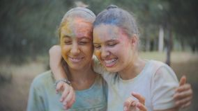 De waternevel van twee van tieners omvat in Holi-verf in het Park na Holi-festival stock video