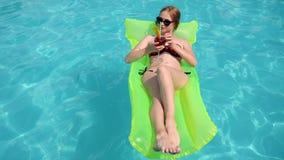 De waterpartij, meisje in bikini ligt op opblaasbare strandmatras in poolside, wijfje in badpak met kleurrijk stock video