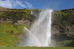 De waterval en de regenboog van IJsland Stock Foto's