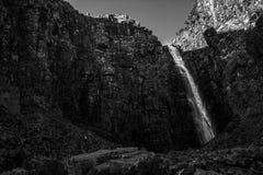 De waterval stroomt onderaan de grote steenmuur Stock Foto's