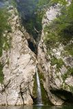 De waterval van een spleet met een rots valt in het meer stock foto's