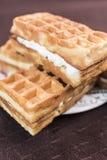 De Weense wafels met vanille-room het vullen zijn op een schotel op een donkere bruine achtergrond Stock Foto