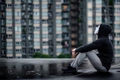 De weerspiegeling van geheimzinnigheid hoodie bemant in wit masker koesterend zijn knieën zittend in de regen op dak van de verla stock afbeelding