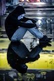 De weerspiegeling van geheimzinnigheid hoodie bemant in wit masker koesterend zijn knieën zittend in de regen op dak van de verla stock foto