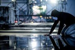 De weerspiegeling van geheimzinnigheid hoodie bemant in wit masker voelend het schuldige kijken zijn gezicht op natte vloer terwi stock afbeeldingen