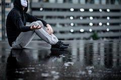 De weerspiegeling van geheimzinnigheid hoodie bemant in witte maskerzitting in de regen op dak van de verlaten bouw Bipolaire wan stock afbeelding