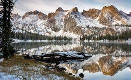 De weerspiegeling van het meer van bergen en de logboekwinter stock fotografie