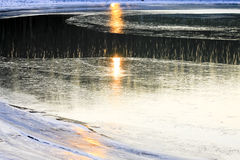 De weerspiegeling van zonlicht op de ijzige kust Stock Foto