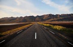 De weg aan de horizon in IJsland Het typische landschap van IJsland met weg en bergen Jonge volwassenen stock afbeelding