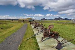 De weg aan landbouwbedrijfhuizen in Modrudalur-regeling van Oostelijk Eiland, oude landbouwmachine voor grondcultuur is geïnstall stock afbeeldingen