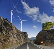De weg, de windmolens en de bergen stock fotografie
