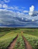 De weg die neer van de heuvel leiden stock foto
