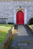 De weg die tot een rode houten deur in een oude steenkerk leiden bouwt Stock Afbeeldingen