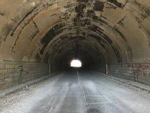 De weg door een donkere rechte overspannen die tunnel van steen, in de berg wordt gemaakt Helder Licht aan het eind van royalty-vrije stock afbeelding