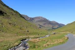 De weg en Gatesgarthdale Beck Cumbria van de Honisterpas Stock Fotografie