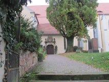 De weg en de ingang aan een oud privé huis stock afbeelding