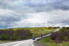 De weg gaat ver weg in de afstand, horizon, weinig auto's, groen gebied en bos, bewolkte blauwe hemelachtergrond stock foto