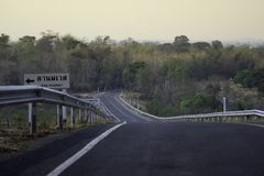 De weg heeft een gele lijn en er is een waarschuwingsbord neer op de steile linkerkant van hem royalty-vrije stock afbeeldingen