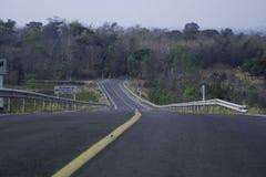 De weg heeft een gele lijn en er is een waarschuwingsbord neer op de steile linkerkant van hem royalty-vrije stock foto