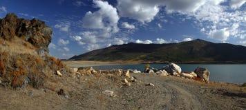 De weg langs de kust van een bergmeer stock foto