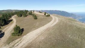 De weg op de heuvel met sparren dichtbij steile helling met een vallei en een kuststad op blauwe hemelachtergrond schot lucht stock footage