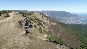 De weg op de heuvel met sparren dichtbij steile helling met een vallei en een kuststad op blauwe hemelachtergrond schot lucht stock video