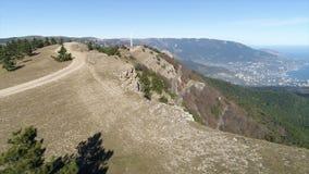 De weg op de heuvel met sparren dichtbij steile helling met een vallei en een kuststad op blauwe hemelachtergrond schot lucht stock afbeelding