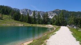 De weg rond een meer van waterreserves in Oostenrijkse hoogte alpien bergen Royalty-vrije Stock Foto's