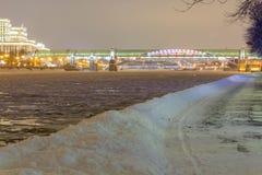 De weg in de sneeuw drijft dichtbij de rivier in het park in de avond af stock afbeelding