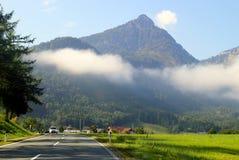 De weg tussen groene weiden met de bergen in de wolken op de achtergrond in de zonnige dag Royalty-vrije Stock Foto's