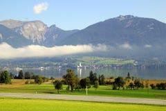 De weg tussen groene weiden met de bergen en een meer in de wolken op de achtergrond in de zonnige dag Stock Fotografie