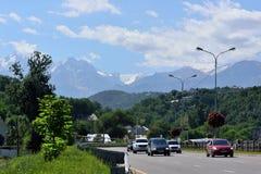 De weg van Alma Ata met groene heuvels en Alatau-bergen op de achtergrond Stock Foto