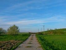 De weg van concrete panelen, tussen gebieden wordt gemaakt, gaat over een brug, blauwe hemel op achtergrond die royalty-vrije stock afbeeldingen