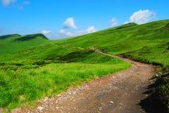 De weg van de berg aan verre groene heuvels stock foto's
